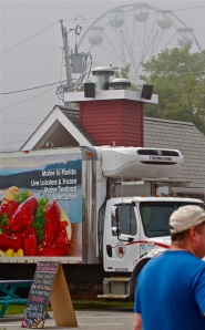 A Linda Bean Perfect Maine Lobster truck parked in front of the Lobster Cooker with Maine Lobster Festival Ferris Wheel Cloaked in Fog in the Background
