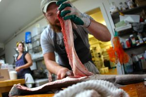 Chef Max Miller of the Landings Restaurant in Rockland, Maine, filleting locally-sourced fish.